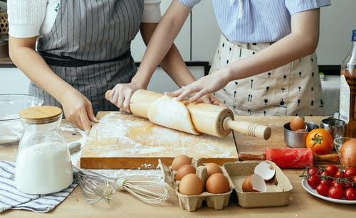 Crop women rolling dough on board