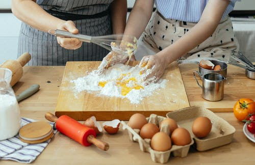 Crop women mixing egg and flour with whisk