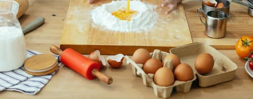 Unrecognizable person mixing egg into flour at table with wooden board rolling pin and kitchenware in light kitchen while cooking