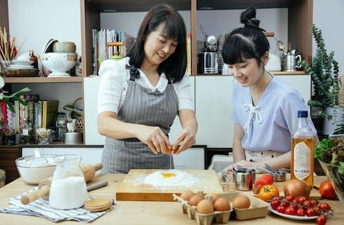 Smiling Asian women with egg preparing dough