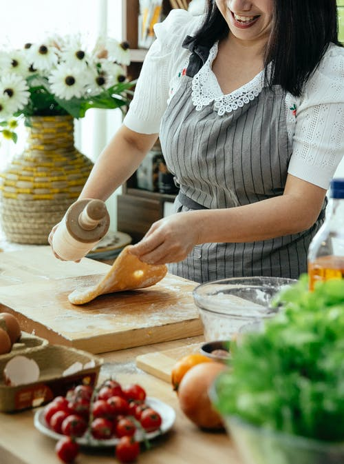Unrecognizable female cook in apron standing at table with wooden board while rolling dough in kitchen with flowers in vase