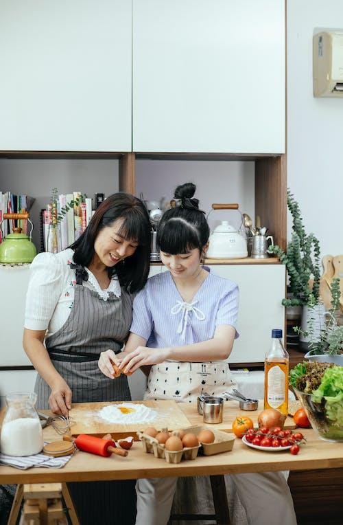Cheerful Asian women adding egg to flour