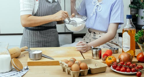 Unrecognizable female cooks with bowl of flour standing at table with cutting board and various ingredients in kitchen while making dough