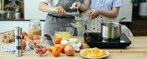 Crop women cooking pasta in kitchen