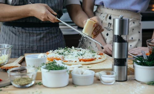 Unrecognizable female cooks grating cheese on homemade pizza at table with various ingredients and condiments in kitchen during cooking process