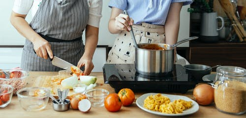 Unrecognizable woman cutting fresh tomato on cutting board while standing at table with ingredients and stove near female cook stirring sauce in pan
