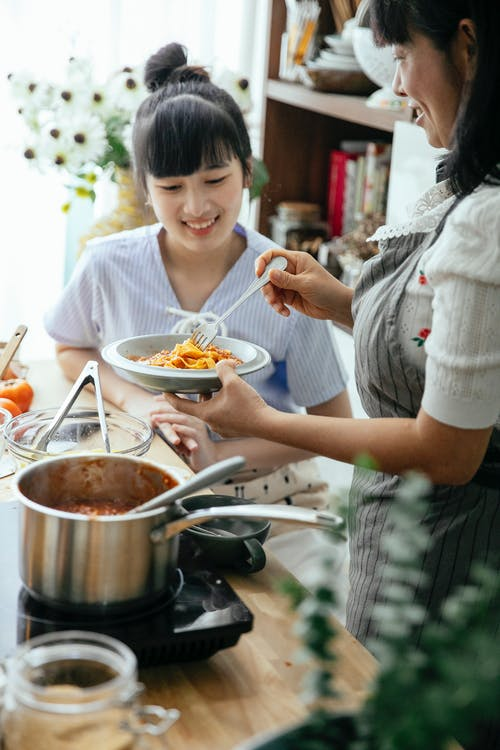 Happy Asian women with dish in plate