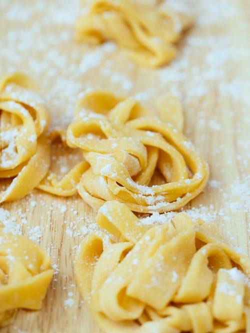 Closeup of fresh uncooked pasta with sprinkled flour placed on wooden board in kitchen during cooking preparation against blurred background
