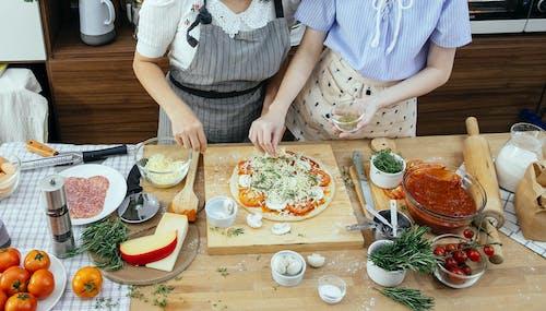 Crop women adding spices on pizza