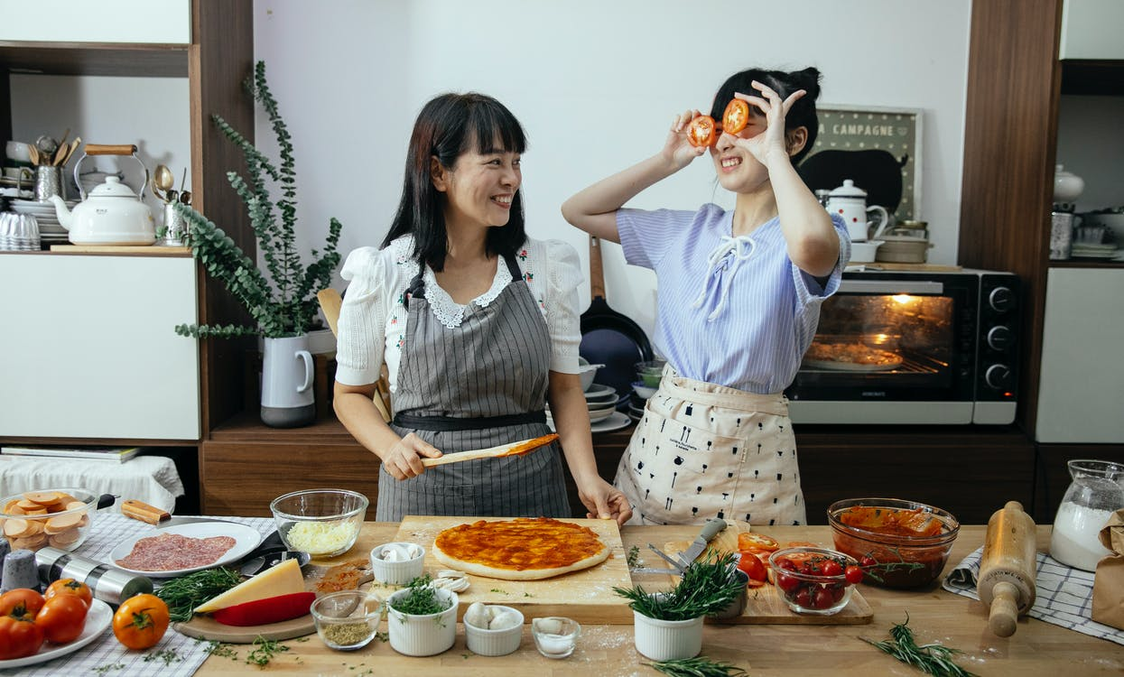 Smiling Asian woman spreading tomato sauce on pizza dough while looking at funny female covering eyes with tomato slices in kitchen