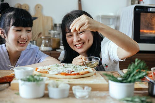 Cheerful Asian women sprinkling seasoning on pizza
