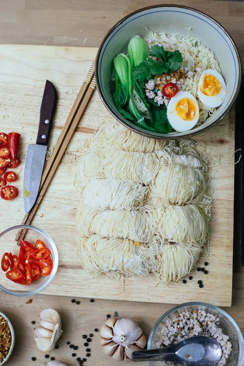 Top view of tasty ramen served in bowl with eggs and greens on wooden board with uncooked noodles cutlery and and chili pepper
