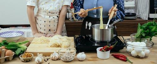 Crop women cooking pasta together