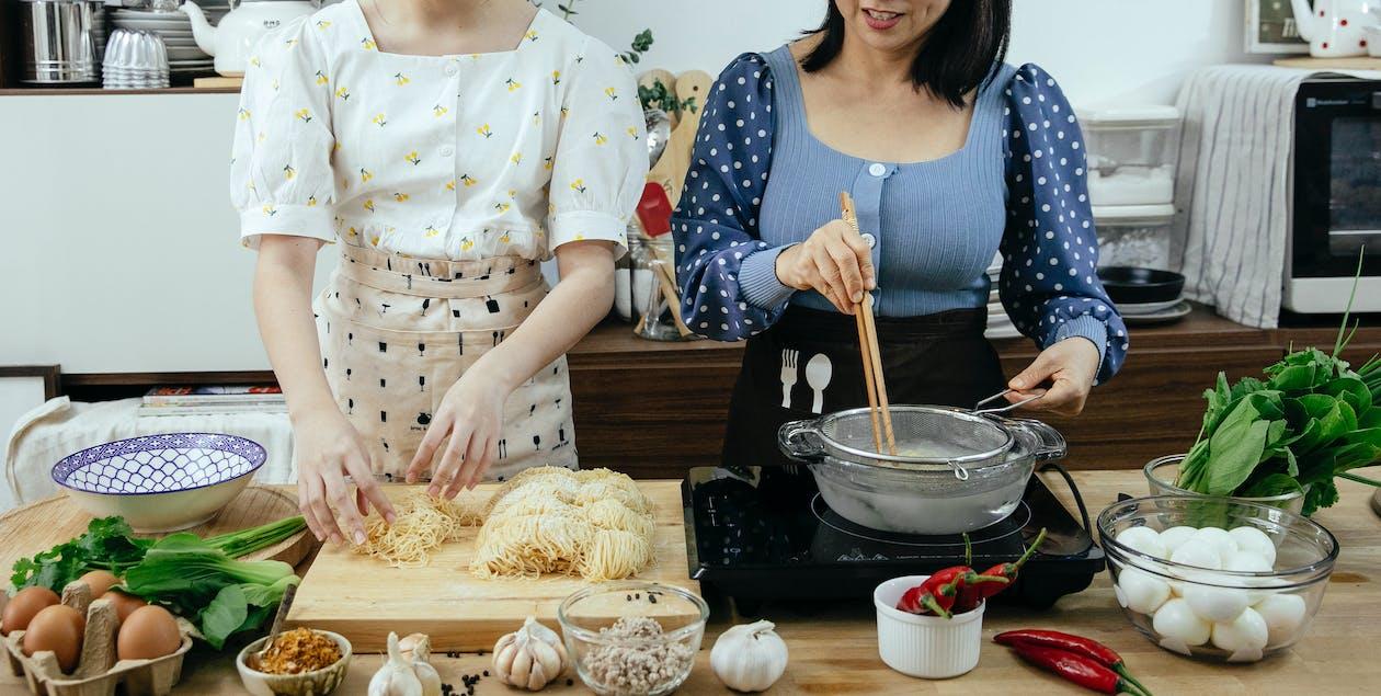 Crop women cooking noodles in kitchen