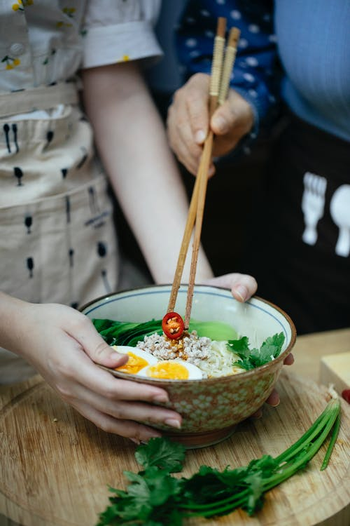 Unrecognizable female cooks with chopsticks putting chopped chili pepper in bowl with ramen topped with boiled eggs and greens during lunch
