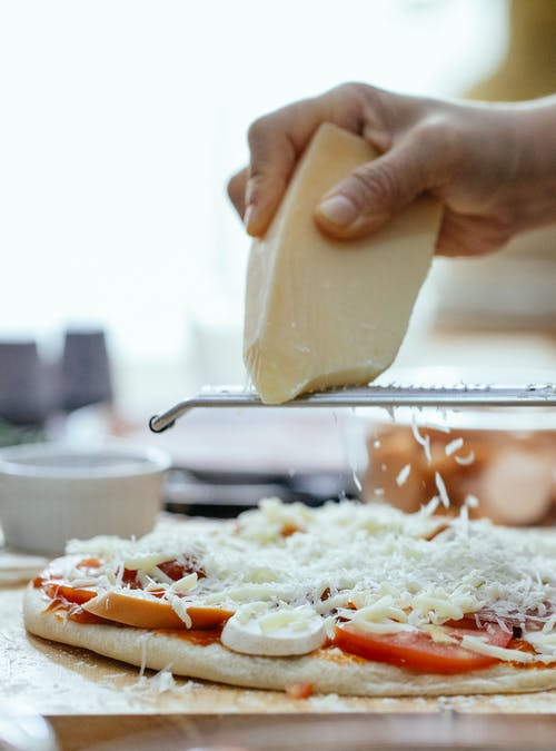 Unrecognizable cook grating cheese on raw pizza with toppings placed on table during cooking process in kitchen against blurred background