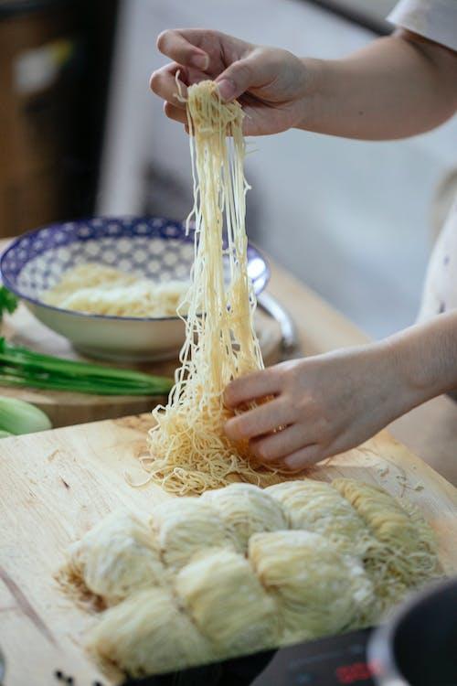Crop person making pasta in kitchen