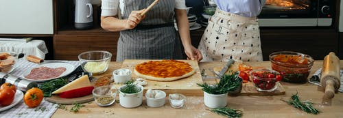 Crop anonymous female cooks at table with tomato salsa on raw dough near assorted ingredients for pizza in house