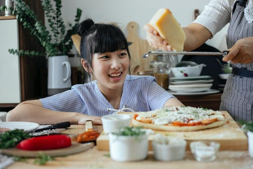 Crop anonymous woman grating Parmesan cheese above raw pizza while cooking near cheerful ethnic daughter in kitchen at home