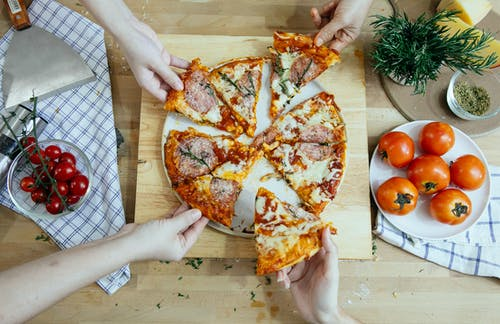 Crop friends taking slices of delicious pizza from cutting board