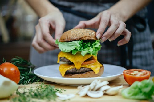 Faceless female chef preparing delicious double cheeseburger with bread buns and meat patties between fresh vegetables and herbs at home