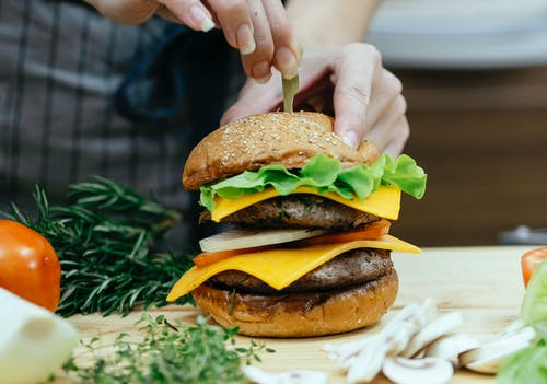 Crop unrecognizable female chef inserting skewer into bread bun while preparing delicious cheeseburger between assorted ingredients at home