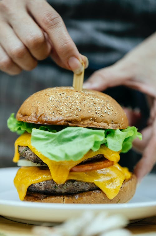 Crop cook inserting stick into delicious cheeseburger in kitchen