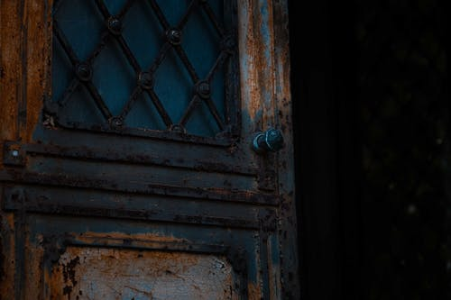 Low angle of opened shabby metal door of derelict damaged worn out house