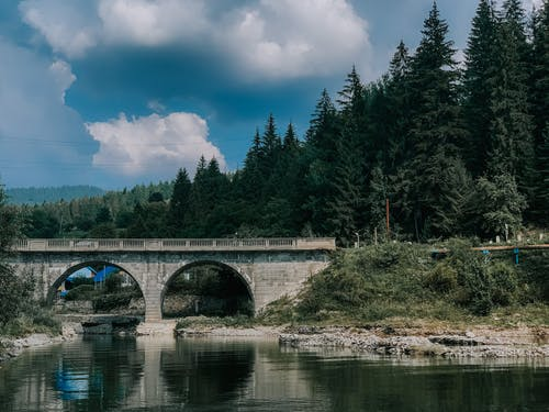 Picturesque scenery of big stone arched bridge over calm rippling river between lush coniferous trees on clear summer day