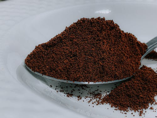 Closeup aromatic organic ground coffee heaped in silver teaspoon on white ceramic plate on table in cafeteria kitchen