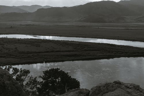 Scenic black and white view of high mountains against dry terrain with shrubs and rippled river