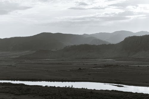 Black and white of mountains against river and dry land under shiny sky with clouds