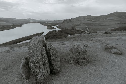 Black and white of boulders on dry terrain against river and ridges under cloudy sky