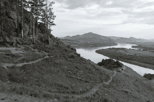 Black and white of mounts with grass and narrow paths against wavy river in daytime