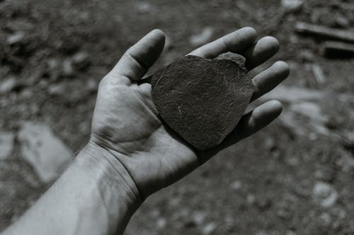 Black and white overhead of crop anonymous male with uneven stone in hand in nature