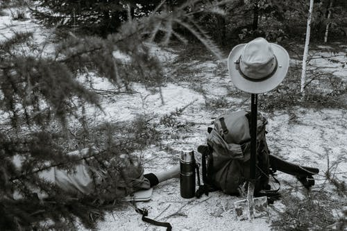 Unrecognizable traveler lying on ground near tree and backpack