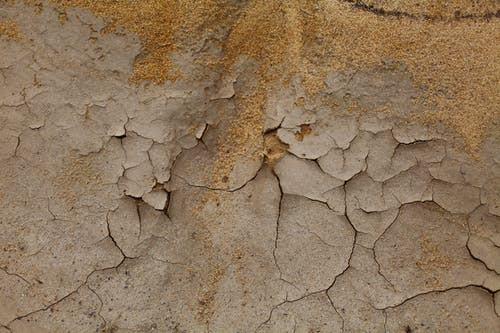 Top view of dry uneven cracked surface near sandy terrain in daylight in desert area