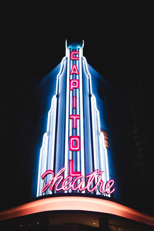 Exterior of illuminated building with shiny signboards at night