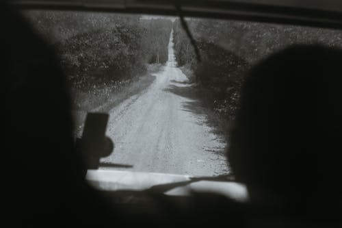Anonymous travelers driving vehicle on countryside road
