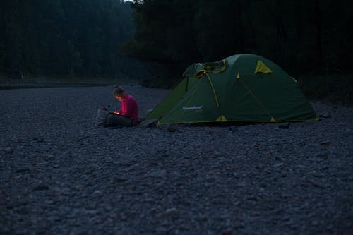 Anonymous tourist watching gadget near tent at night