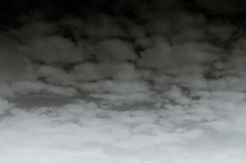 Black and white scenic view of abstract backdrop of sky with fluffy clouds in daylight