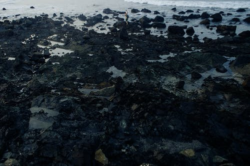 High angle rough sharp black stones on sandy wet beach washed by foamy waving sea