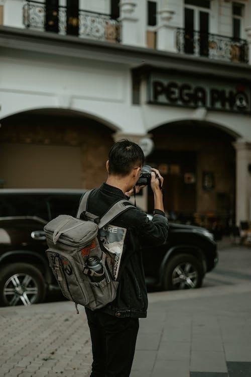 Man in Black Jacket Holding DSLR Camera