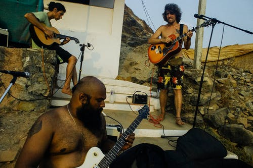 Local musical band of ethnic males in casual wear playing guitars outside shabby house in rural location