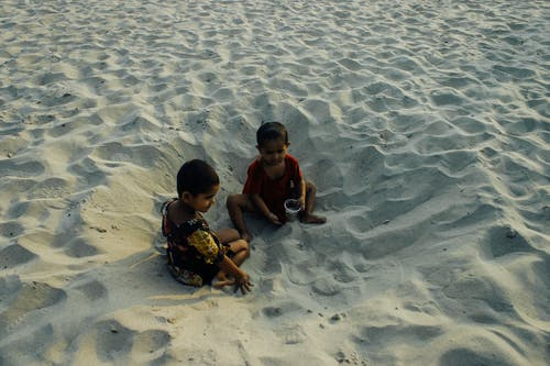 Full body content little Asian siblings in casual clothes sitting on sandy vast beach and playing together