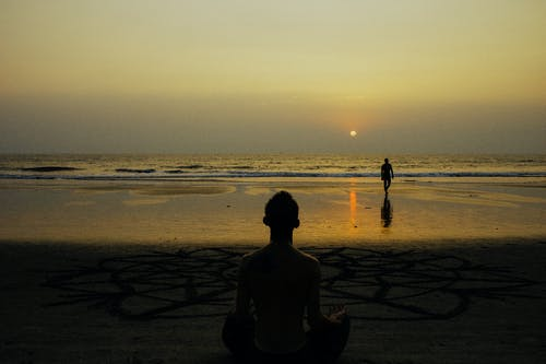 Back view male silhouette siting on Lotus pose and meditating on sandy beach near mandala drawing against tranquil seawater at picturesque sunset