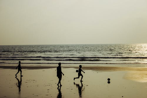 Children silhouette playing football on wet seashore at sunset