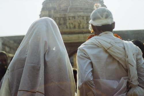 Unrecognizable couple in white traditional clothes during wedding ceremony