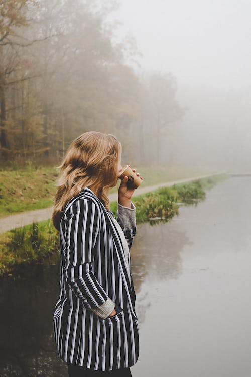 Woman in Black and White Striped Long Sleeve Shirt Standing on Gray Concrete Road