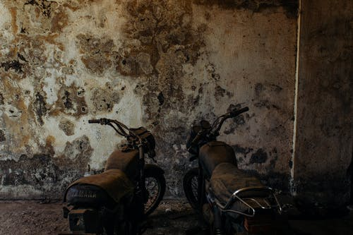 Old retro motorbikes standing on dusty ground near weathered uneven stone wall in daylight